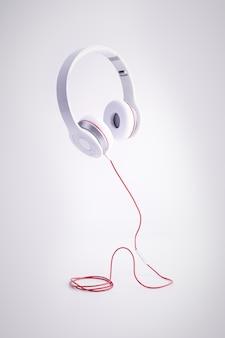 Foto vertical de fones de ouvido brancos com um cabo vermelho