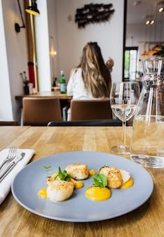 Foto vertical de frango e camarão com molho especial num prato redondo azul