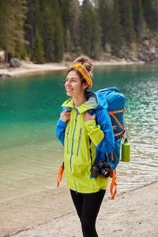 Foto vertical de garota turista caminhando pelo lago turquesa, floresta de coníferas, sorrindo alegremente segurando a câmera e uma mochila grande