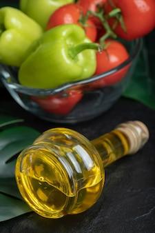 Foto vertical de garrafa de azeite na frente de legumes frescos.