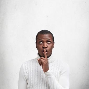 Foto vertical de homem negro afro-americano mantém o dedo da frente nos lábios e pede para manter as informações em segredo