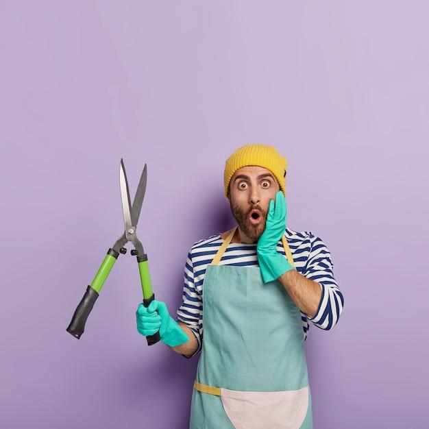 Foto vertical de jardineiro estupefato posando com uma tesoura grande