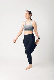Foto vertical de jovem está se exercitando e se alongando um pouco em um estúdio branco.