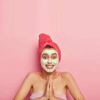 Foto vertical de jovem feliz aplica máscara de limpeza no rosto, mantém as palmas das mãos pressionadas, pede ajuda, recebe tratamentos de beleza, usa toalha enrolada na cabeça, pele saudável, se preocupa com a higiene