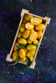 Foto vertical de kumquats orgânicos em uma caixa de madeira sobre uma superfície azul