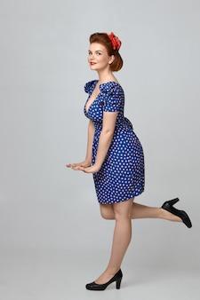 Foto vertical de linda jovem ruiva usando sapatos pretos de salto alto e vestido azul pontilhado com decote decotado posando, segurando as mãos na frente dela e mantendo a perna levantada