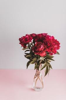 Foto vertical de lindas flores de peônia vermelha frescas em um vaso em uma bela superfície