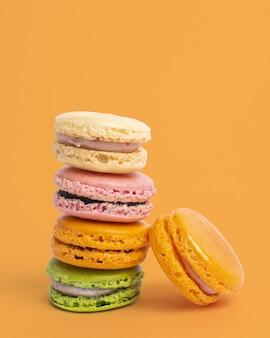 Foto vertical de macaroons coloridos equilibrados contra um amarelo