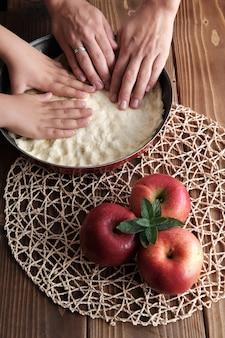 Foto vertical de mãos femininas preparando torta de maçã vermelha