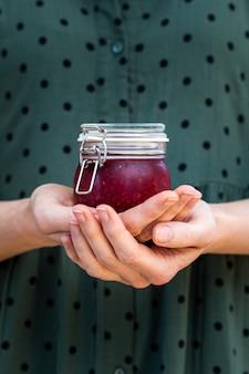 Foto vertical de mãos femininas segurando uma geléia de framboesa crua vegan caseira em uma jarra de vidro