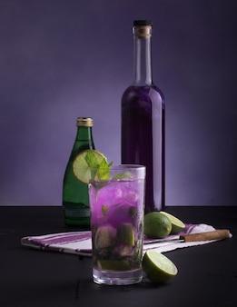 Foto vertical de mocktail de feriado saudável com limão e garrafas ao lado