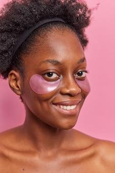 Foto vertical de modelo feminino encaracolado de pele escura aplicando adesivos de hidrogel sob os olhos para rejuvenescimento