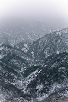 Foto vertical de montanhas cobertas de neve branca durante o inverno