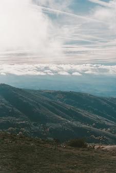 Foto vertical de montanhas sob um céu azul nublado