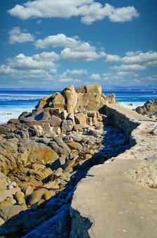 Foto vertical de muitas formações rochosas na praia sob um lindo céu nublado