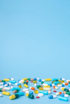 Foto vertical de muitos comprimidos e cápsulas diferentes sobre fundo azul