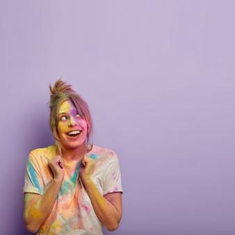 Foto vertical de mulher alegre com uma mistura de tintas coloridas brilhantes, levanta os punhos cerrados, desfruta da tradicional celebração do festival hindu na índia, usa uma camiseta branca casual, com foco acima no espaço livre