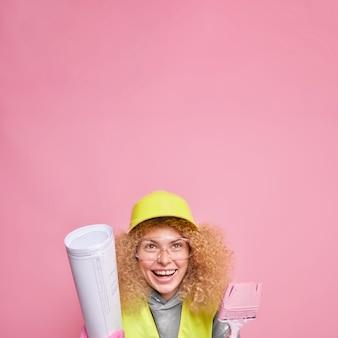 Foto vertical de mulher alegre e cacheada usando óculos transparentes com capacete de segurança segura a planta e um pincel chega no canteiro de obras