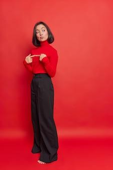 Foto vertical de mulher asiática em pé, indecisa e pensativa, fazendo gesto inseguro, mantendo os dedos indicadores opostos, usando calças de poloneck com fundo de sino preto isolado sobre a parede vermelha
