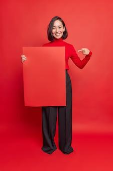 Foto vertical de mulher asiática feliz com cabelo escuro e sorriso agradável aponta para papel quadrado para modelo mostra maquete para seu projeto anuncia banner promocional vestido com roupas elegantes poses internas