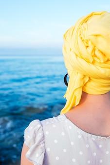 Foto vertical de mulher com um lenço amarelo, apreciando a vista do mar