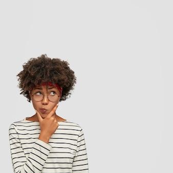 Foto vertical de mulher confusa e hesitante segurando o queixo e franzindo os lábios, olhando para cima sem acreditar, segurando o queixo