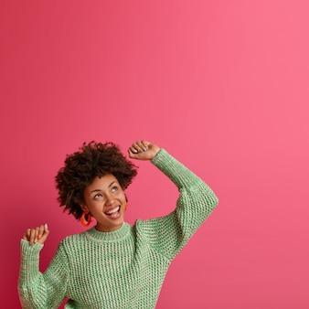Foto vertical de mulher despreocupada otimista levanta as mãos encantada, sente-se muito feliz, olha para cima com expressão sonhadora, sente liberdade nos momentos de lazer, dança ao som da música triunfa sobre algo