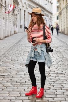 Foto vertical de mulher elegante usando chapéu, macacão listrado, short jeans e botas de borracha vermelha, segura o celular