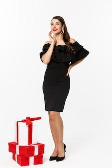 Foto vertical de mulher em pé em um vestido preto elegante com presentes de natal, sorrindo feliz, em pé sobre um fundo branco.