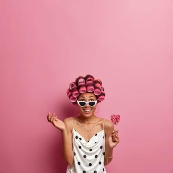 Foto vertical de mulher feliz concentrada acima, levanta a mão e segura pirulito, usa bobes de cabelo e faz um lindo penteado, cuida do cabelo, vestida com vestido de bolinhas e óculos de sol