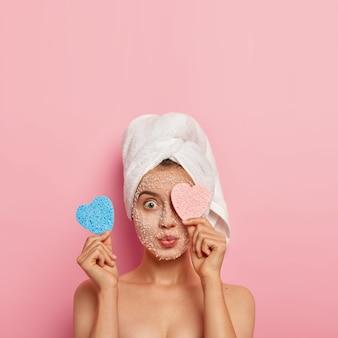 Foto vertical de mulher jovem atônita cobre um olho com esponja cosmética, faz tratamento facial matinal, aplica máscara de sal marinho branco para uma pele perfeita, absorve nutrientes