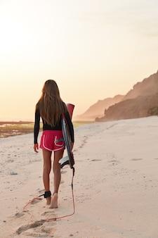 Foto vertical de mulher jovem e desportiva com belas nádegas, caminhando ao ar livre