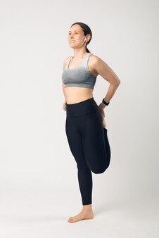 Foto vertical de mulher jovem e magro em roupas esportivas, estendendo-se nas pernas sobre fundo branco