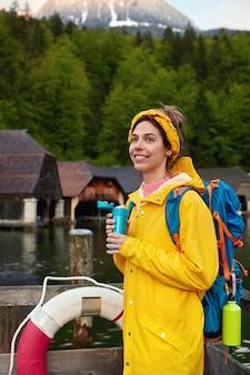 Foto vertical de mulher sorridente em capa de chuva amarela