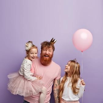 Foto vertical de pai solteiro e duas filhas superemotivos, celebrando o dia dos pais e vestindo roupas festivas