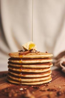Foto vertical de panquecas com calda, manteiga e nozes torradas em uma placa de madeira