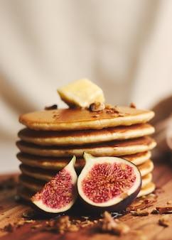Foto vertical de panquecas com calda, manteiga, figos e nozes torradas em um prato de madeira