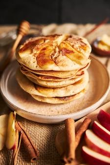 Foto vertical de panquecas de maçã em um prato com fatias de maçã e canela ao lado