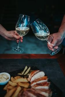 Foto vertical de peito de frango e batatas grelhadas em um prato e vinho