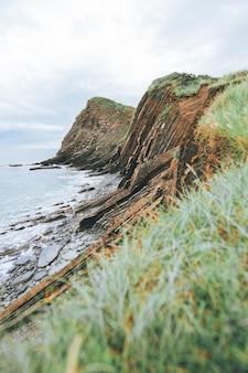 Foto vertical de penhascos cheios de grama verde ao lado do mar azul durante o dia