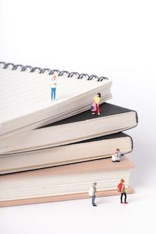 Foto vertical de pequenas estatuetas de alunos em pé sobre os livros didáticos