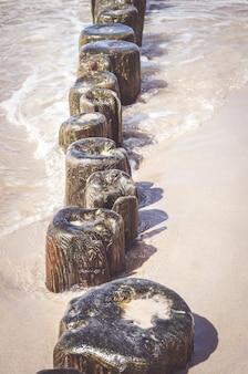 Foto vertical de pequenas pranchas de madeira em uma costa arenosa