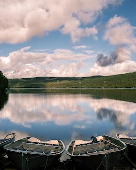 Foto vertical de pequenos barcos na margem de um lago com o reflexo do céu na superfície da água