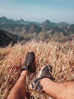 Foto vertical de pés masculinos e a vista das montanhas no rio de janeiro