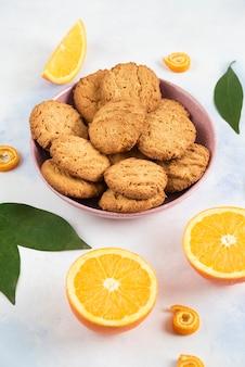 Foto vertical de pilha de biscoitos em uma tigela e meio corte de laranjas.