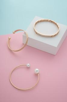 Foto vertical de pulseiras de ouro modernas sobre fundo de papel em tons pastel