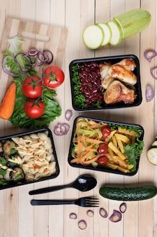 Foto vertical de recipientes de plástico preto de alimentos. vista superior na mesa de madeira, refeição pronta
