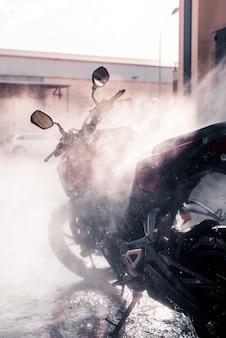 Foto vertical de respingos de água pressurizada na motocicleta durante a lavagem.