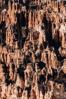 Foto vertical de rochas em um desfiladeiro sob a luz do sol