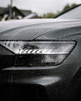 Foto vertical de sabonete em um carro preto moderno e brilhante durante o dia
